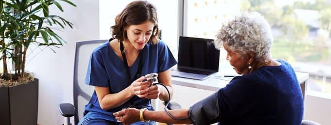 caregiver checking senior womans blood pressure