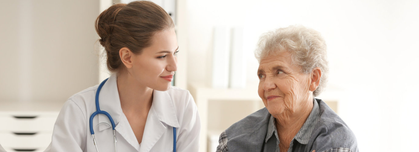 nurse and senior woman looking at each other