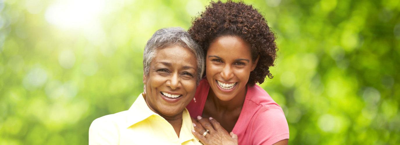 female caregiver hugging senior woman outdoor