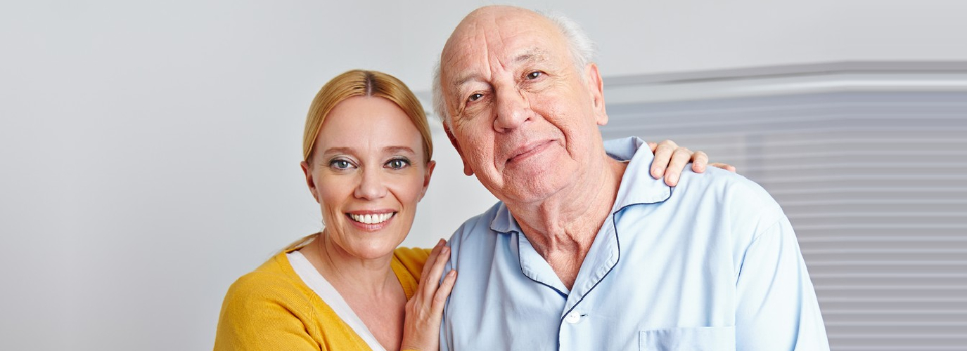 beautiful caregiver hugging senior man indoor